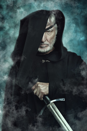 espadas medievales: Un guerrero de ojos con el cabo negro y espada. La fantas�a y la mitolog�a Foto de archivo