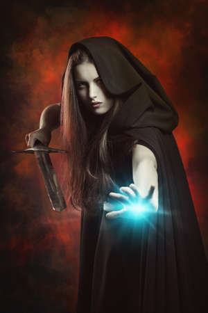 Beautiful sorceress in fighting position with sword . Fantasy and magic