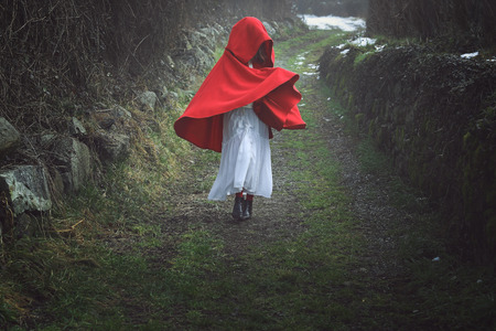 Surreal  portrait of a red hooded woman on a dark country trail Stock Photo