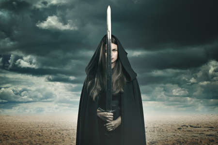 surreal: Beautiful dark woman with sword in a desert and stormy landscape. Fantasy and surreal