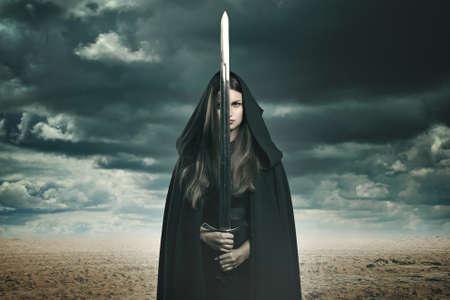 espadas medievales: Mujer morena hermosa con la espada en un desierto y el paisaje tormentoso. Fantas�a y surrealista