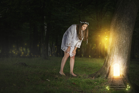 wood nymph: Beautiful young woman finds the door to fairy realm . Fantasy concept