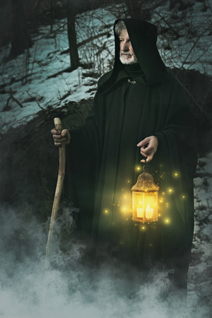 Hermit of the forest with lighted lantern . Wisdom and tarot conceptual Stock fotó