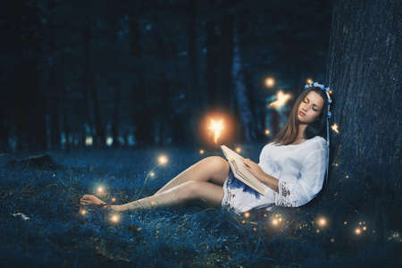 soñando: Hermosa mujer durmiendo pacíficamente entre las hadas del bosque. La magia y la fantasía