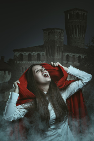 Dark portrait of a red hooded vampire . Creepy castle as background