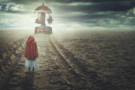 dark red: Red hooded woman on a strange beach with toy carousel. Fantasy and surreal