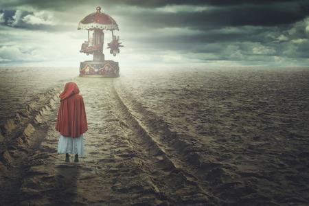 Rode hooded vrouw op een vreemde strand met speelgoed carrousel. Fantasie en surrealistische Stockfoto