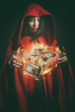 red horse: Red hooded woman with magical wooden toy . Fantasy and surreal