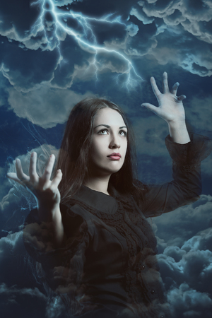 Beautiful witch calls the power of storm . Fantasy and magic Stock Photo