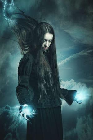 mago: Bruja morena llamando poderes de trueno. Fantasía y surrealista tiro del estudio Foto de archivo