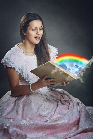 Beautiful woman with surprise expression opens a magical book . Surreal and fantasy photo