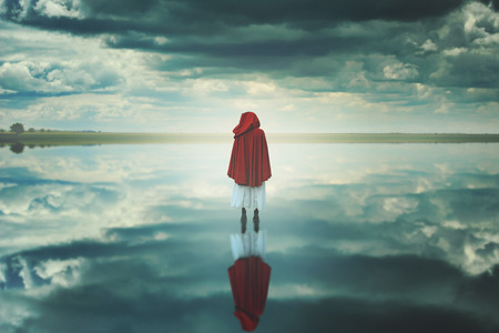 Red hooded woman in a strange landscape with clouds. Fantasy and surreal