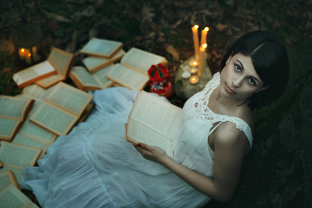 Beautiful pale woman among open books in a dark forest. Surreal and weird photo