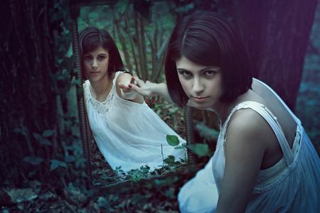 Mooie bleke vrouw in een donker bos met een vreemde spiegel. Surreal en rare