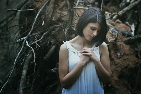 wood nymph: Sad and beautiful woman praying among dead tree roots . Dark fantasy Stock Photo