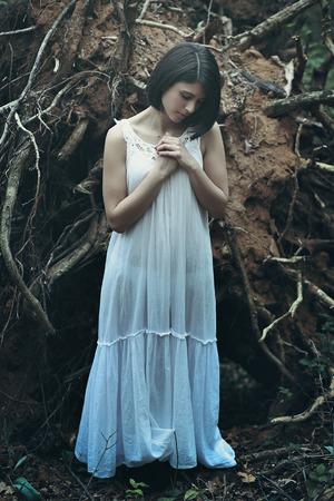 heathen: Beautiful woman with eyes closed praying among dead trees . Dark fantasy
