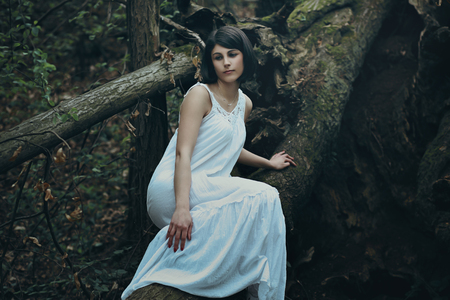 Beautiful woman with sad expression posing on a dead tree . Dark romance