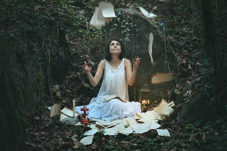 Woman in dark wood surrounded by books and pages . Surreal and weird Stock Photo