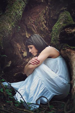 madre tierra: Mujer pensativa entre ra�ces de �rboles oscuros. Madre abrazo tierra