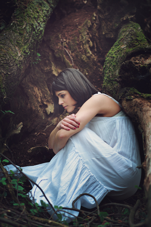 mother earth: Thoughtful woman among dark tree roots . Mother earth embrace