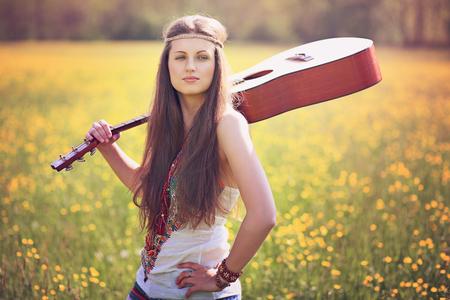 mujer hippie: Mujer hermosa del hippie con la guitarra en un campo de verano. La paz y la armon�a