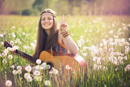 Smiling hippie woman giving peace sign. Freedom and harmony Standard-Bild