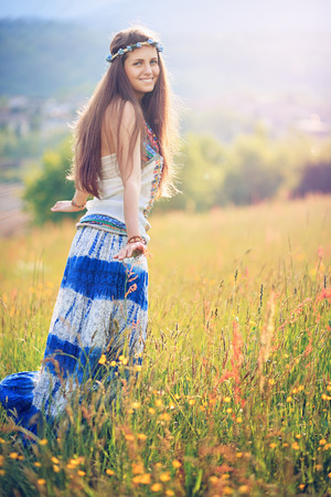 gypsy woman: Happy gypsy woman among wild flowers. Freedom and nature Stock Photo