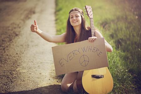 mujer hippie: Mujer del Hippie en un camino rural autostop. Viajes y libertad Foto de archivo