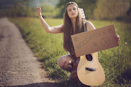 Beautiful hippie with guitar hitch-hiking for Woodstock . Warm summer tones Stock Photo