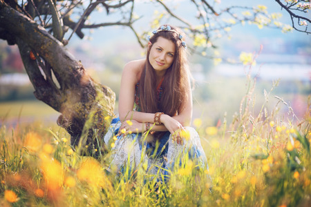 gypsy woman: Smiling gypsy woman posing among flowers . Peace and harmony