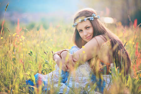 hippie: Beautiful romantic woman in flower field . Hippie and gypsy dress Stock Photo