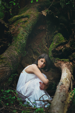 Romantic portrait of a beautiful woman among dark tree roots. Mother earth embrace