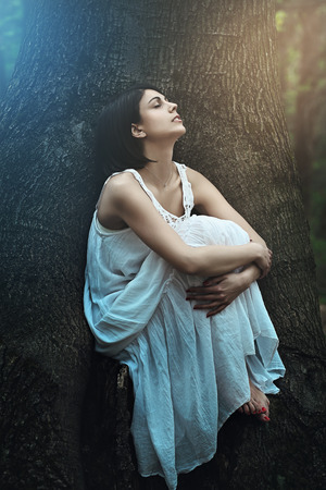 wood nymph: Beautiful woman with eyes closed in a dark forest . Fantasy and surreal portrait Stock Photo