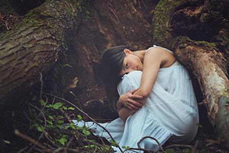 Mooie vrouw onder donkere boomwortels kijkt in de camera. Moeder aarde omhelzing