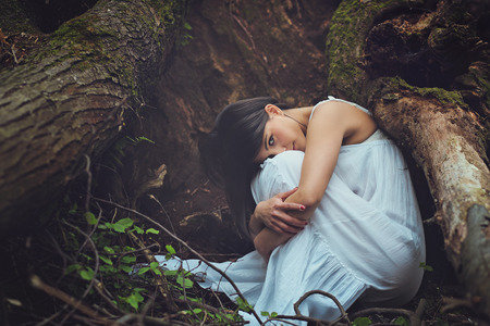 Beautiful woman among dark tree roots looks into camera . Mother earth embrace
