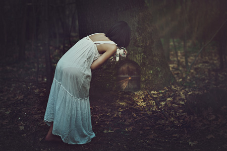 forest wood: Young woman finds a strange door in dark forest . Fantasy and surreal concept