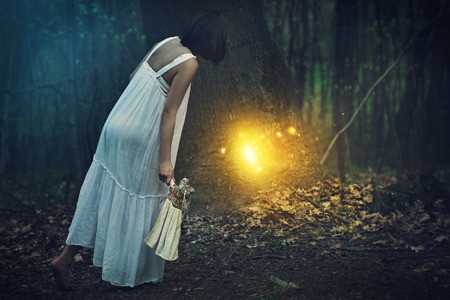 magical forest: Young woman finds entrance to fairies realm in a magical forest . Fantasy concept