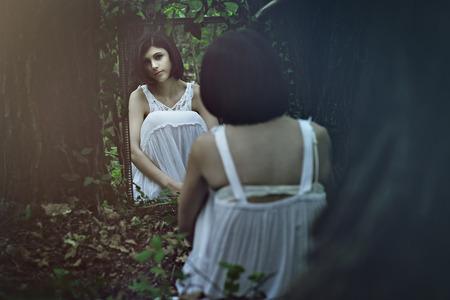 Mooie bleke vrouw voor een spiegel. Surreal en donker Stockfoto