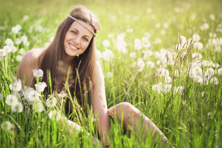 Beautiful young woman smiling in a flowered meadow . Nature harmony and serenity