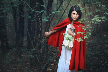 caperucita roja: Mujer hermosa con el manto rojo en un bosque oscuro. Fantasía y surrealista Foto de archivo