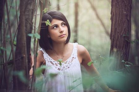 Beautiful woman portrait in soft light forest Standard-Bild