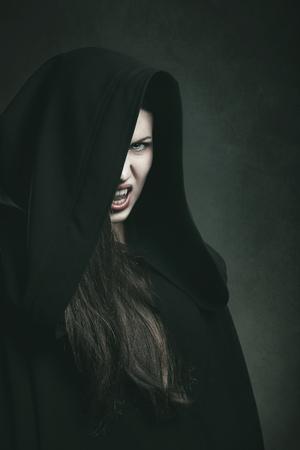 vampire teeth: Dark portrait of a dangerous vampire with black robe . Halloween and horror concept