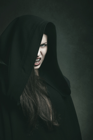 Dark portrait of a dangerous vampire with black robe . Halloween and horror concept