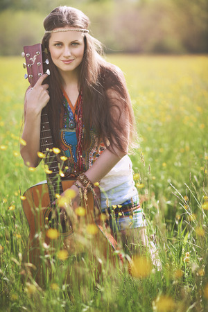 hippie woman: Beautiful hippie woman posing with guitar . Nature harmony Stock Photo
