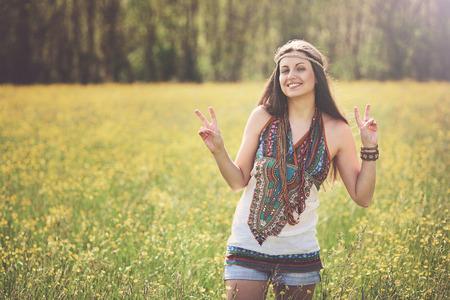 simbolo della pace: Segno di pace da hippie sorridente in un prato. La libert� e l'armonia Archivio Fotografico