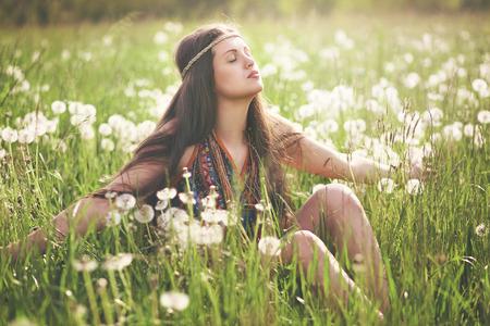 mujer hippie: Mujer hippie hermosa que disfruta de luz del sol en una pradera de flores. Armon�a con la naturaleza Foto de archivo