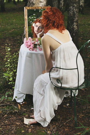 Red hair woman mirror reflection in a forest. Surreal and vintage