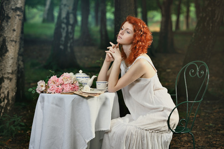 wood nymph: Beautiful redhead woman having tea in the forest . Romantic and victorian portrait Stock Photo