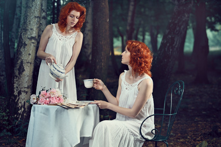 Beautiful redhead woman serving tea to twin . Fantasy and surreal