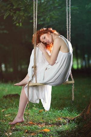girl on swing: Beautiful sad woman on a swing in the forest . Romantic portrait Stock Photo